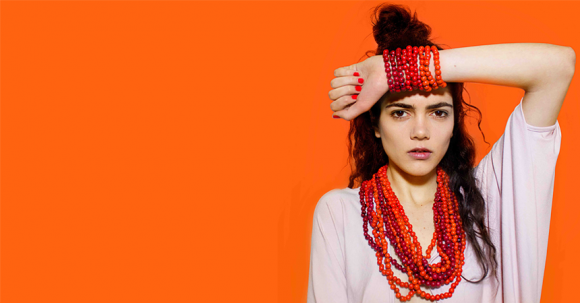 Woman wearing orange bracelets and necklaces standing against orange background.