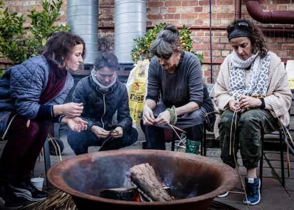 A group of people sitting around a fire and sewing