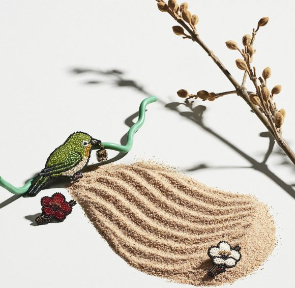 Three brooches on a patch of sand