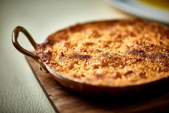 A baked cheese and macaroni dish served in an iron skillet.