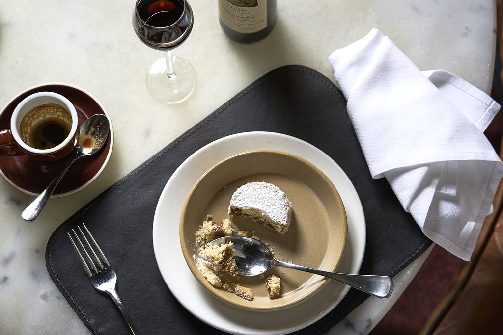A dessert made of biscuits and cream in a bowl with a glass of wine and a espresso coffee on a table