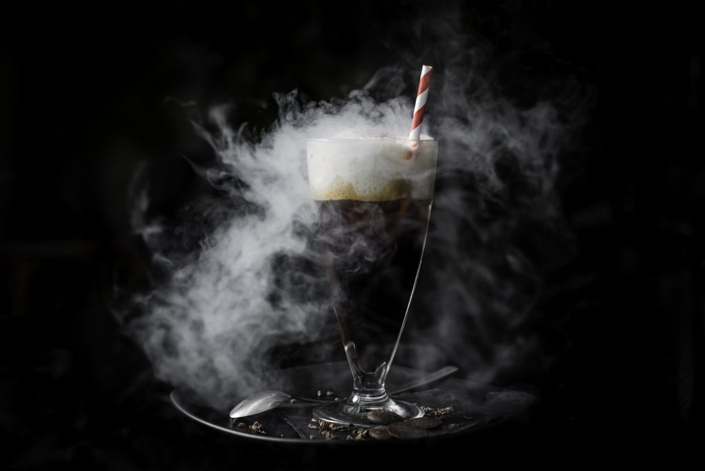 A tall clear glassed filled with dark liquid with a creamy head on top, surrounded by a plume of smoke