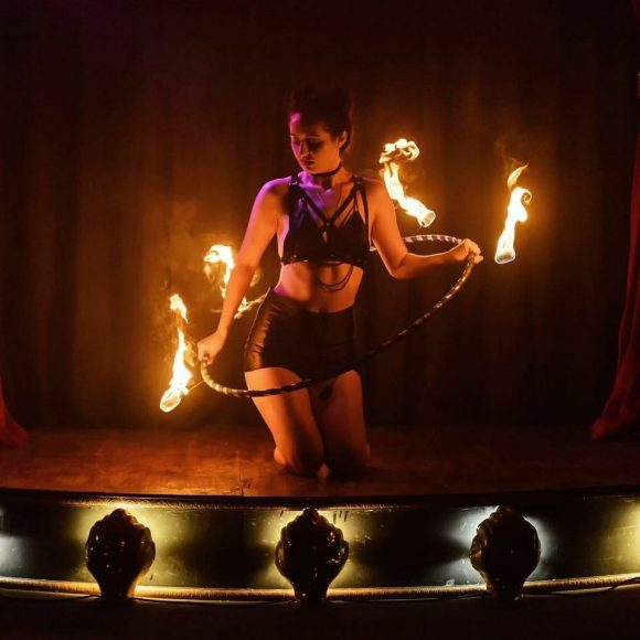 A woman performing on stage with a hoop of fire
