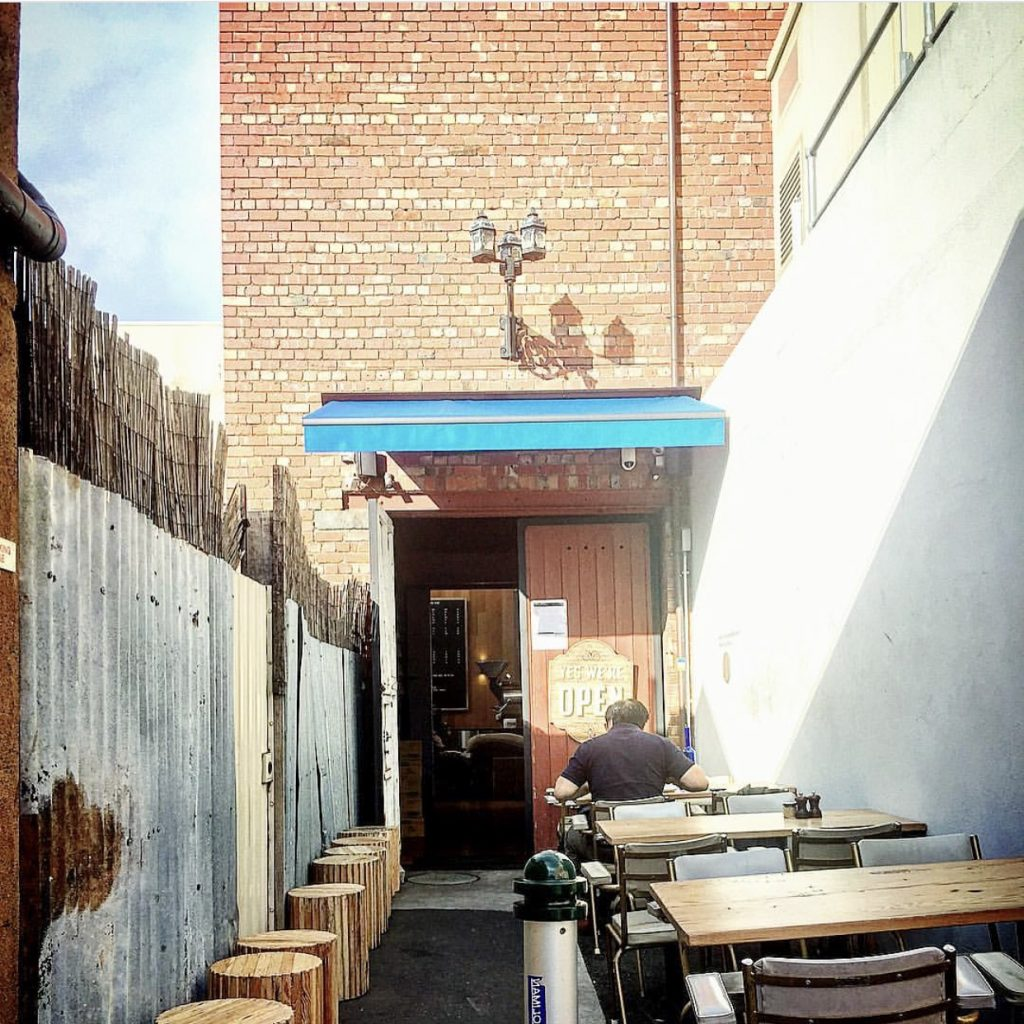 A narrow laneway with tables on either side leading to a cafe