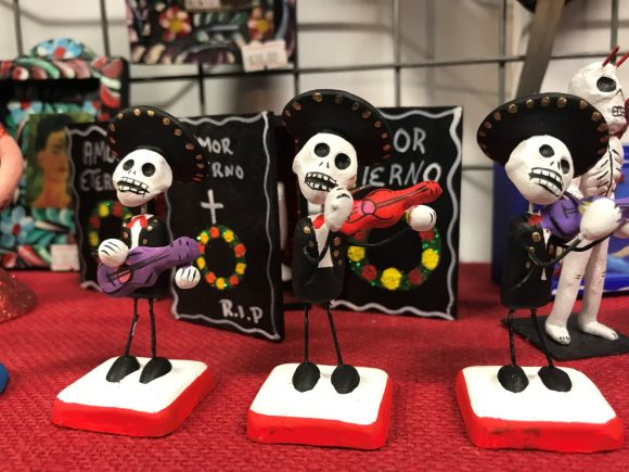 Three Mexican style figurines with skulls for heads and playing the guitar