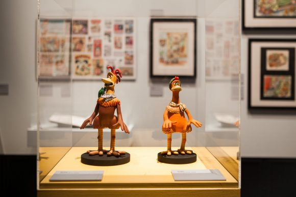 Two plasticine figurines in a glass display case in an exhibition