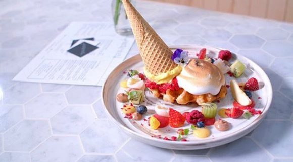 A dessert of fruit, meringue, with an upside down ice cream cone and icecream