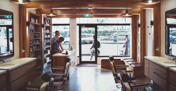 The inside of a barber shop with leather seats and mirrors.