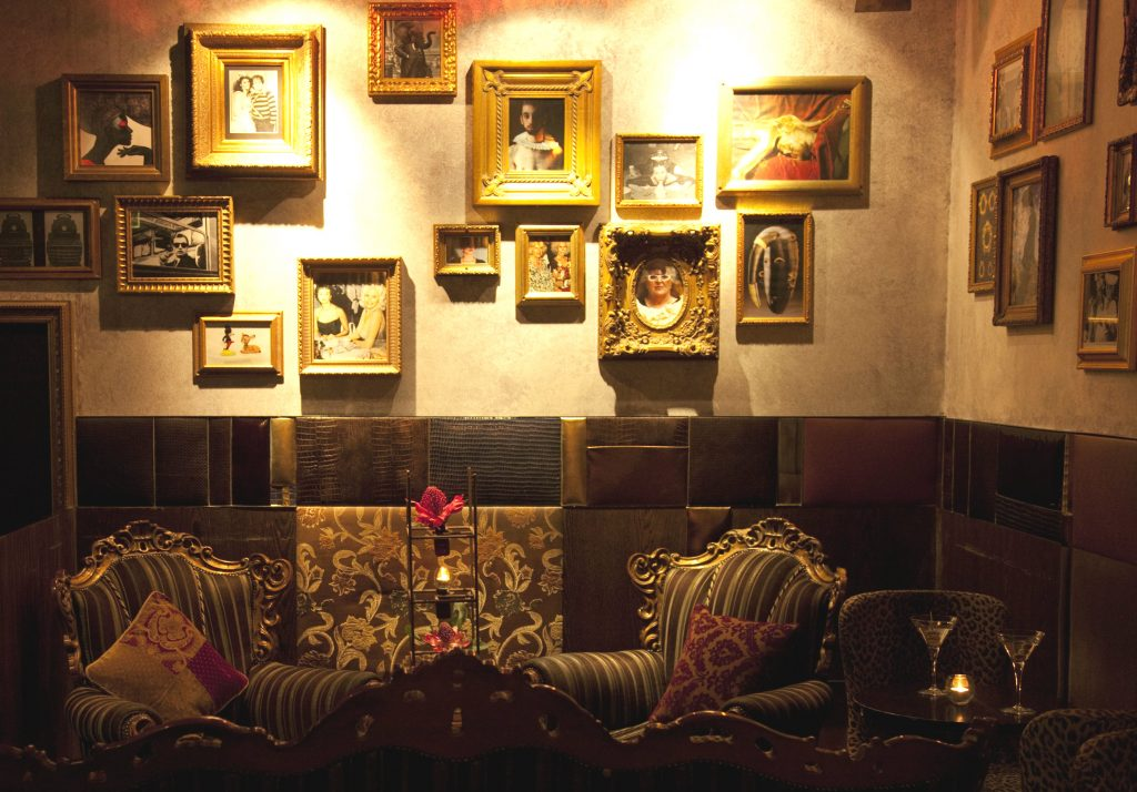 A dark bar with paintings on the walls and elegant couches