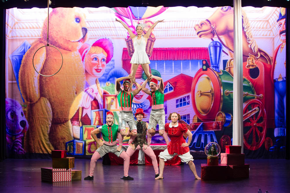 A group of performers dressed like Christmas elves performing an acrobatic trick on stage