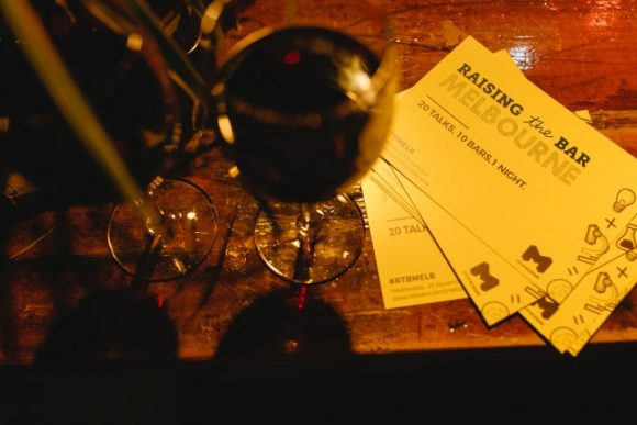 A glass of wine on a table and some tickets