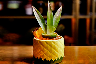 A hawaiian themed cocktail served in a pineapple ceramic jug