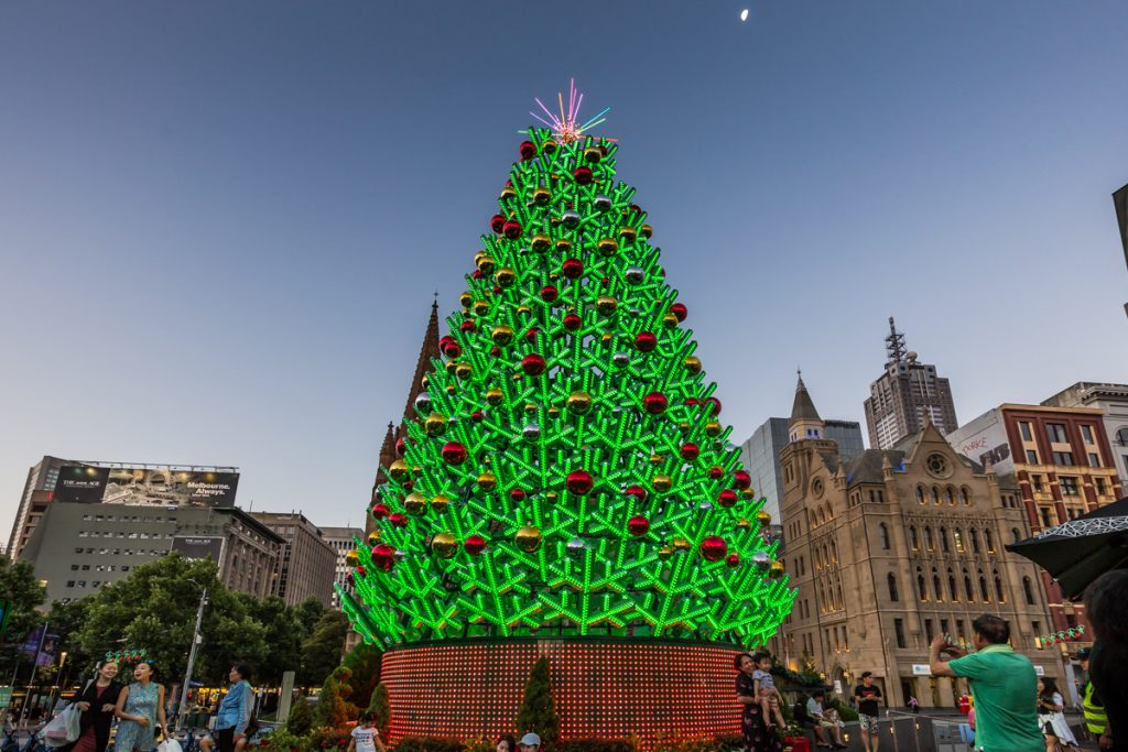 A big artificial Christmas tree against a city backdrop
