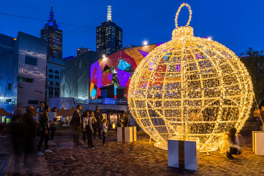 A giant Christmas bauble all lit up in the mdidle of a city square with projections on the building in the background