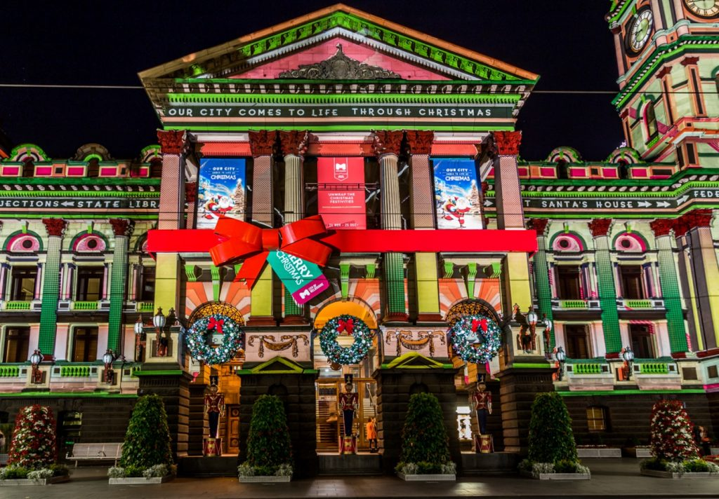 An old building lit up with colourful Christmas themed projections