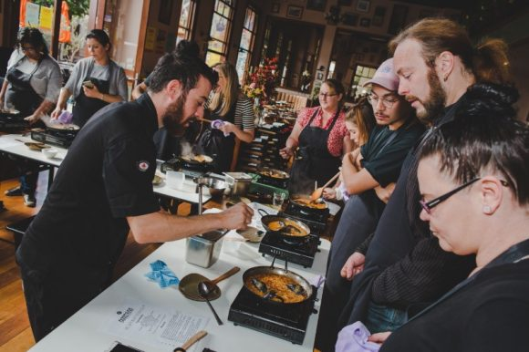 A chef pointing at a pan of paella in front of a group of people