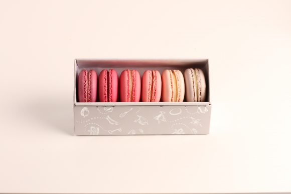 Pink coloured Macaron meringue cookies in an open gift box
