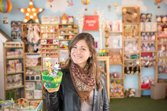A woman holding a toy and smiling with shelves of toys behind her