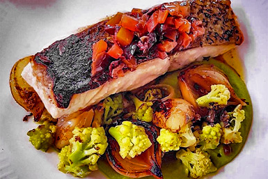 A grilled salmon dish with cauliflower and onions
