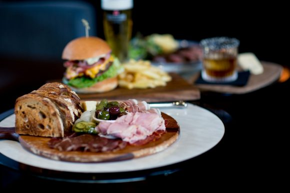 A plate of meat and breads in the foreground, with a burger and chips in the background