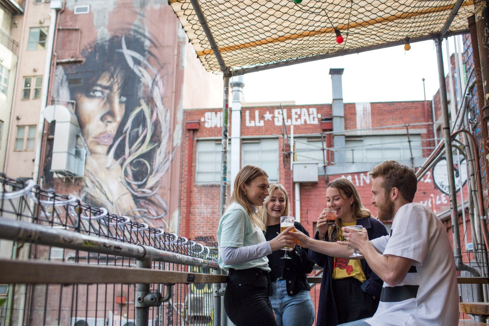 A group of people having drinks on a balcony with a large street art mural in the background