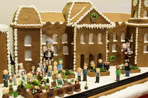 A building created out of gingerbread with people made out of marzipan in front of it