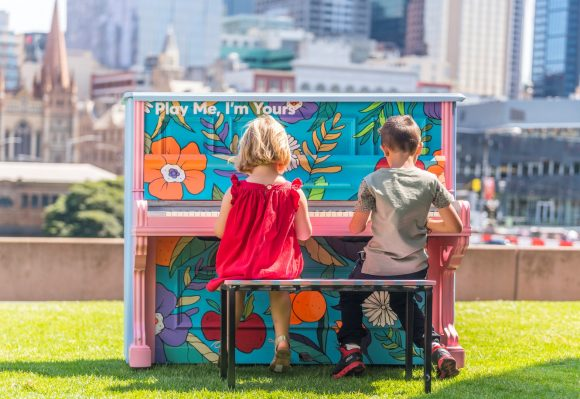 two children playing a piano outside