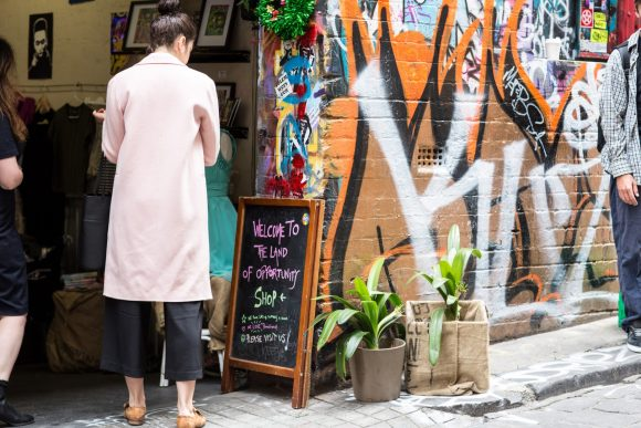 woman looking at a blackboard outside a cafe in a street art covered laneway
