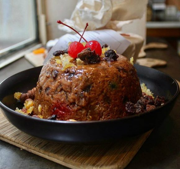 A christmas pudding topped with cherries in a bowl