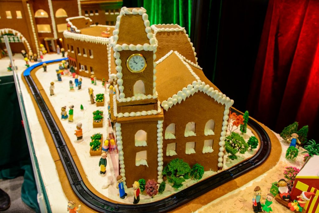 A model of a cathedral made from gingerbread surrounded by mini people made of marzipan