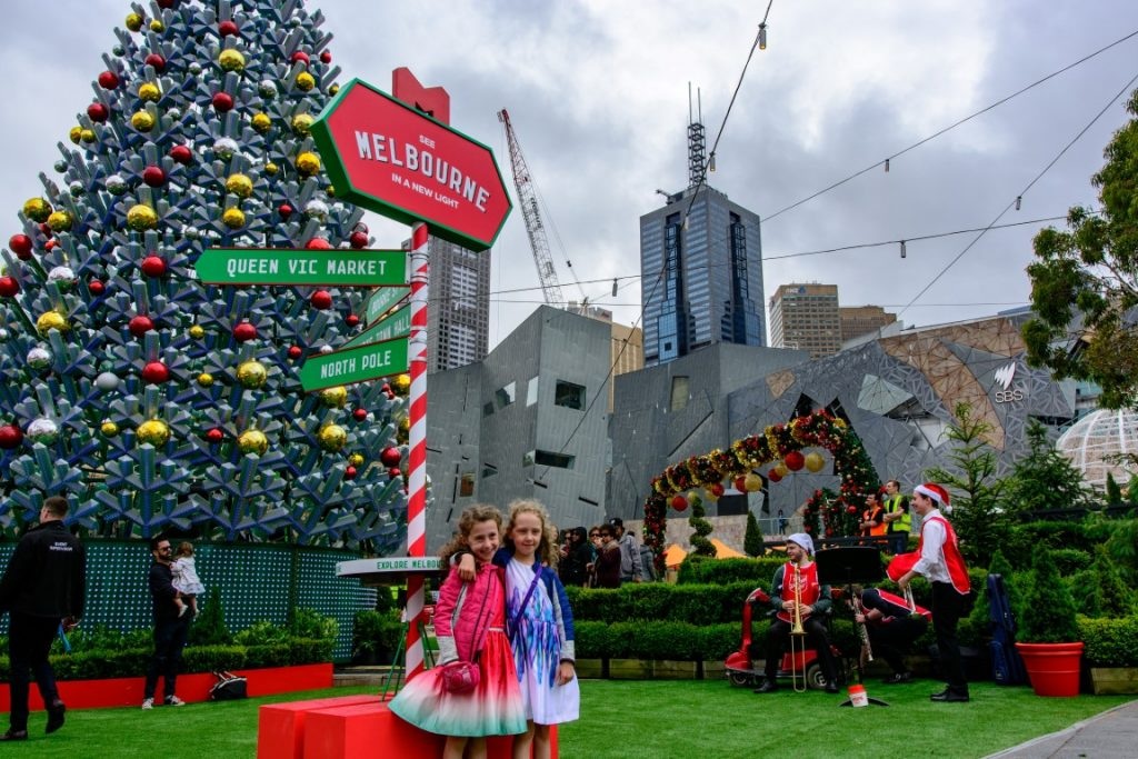 Two little girls standing on astro turf in front of a huge Christmas tree