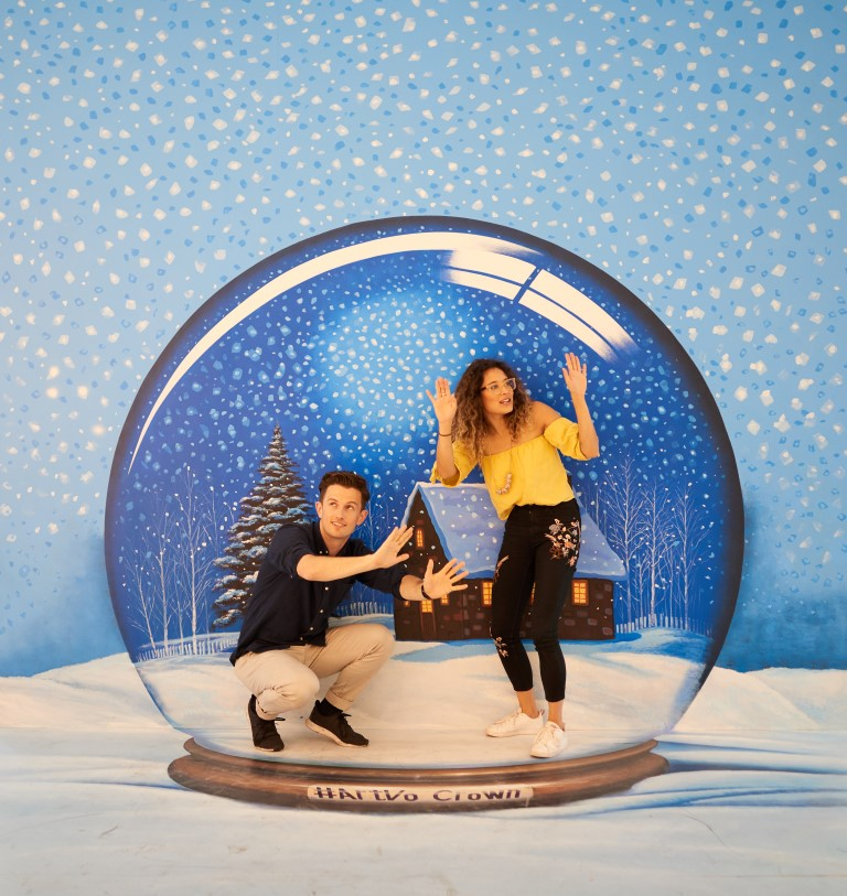 A man and a woman standing inside a giant snow dome