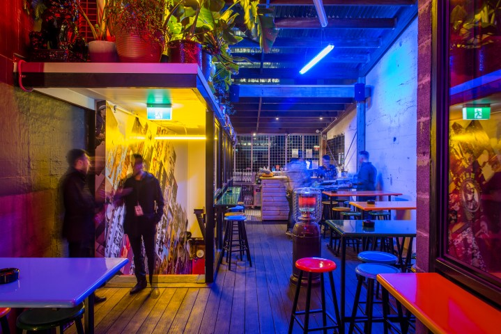 An outdoor rooftop bar with people hanging out under neon lights