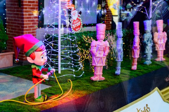 An elf and toy soliders with a Christmas tree in a shop window
