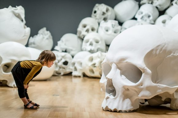 A little girl looking at a giant skulll with more giant skulls behind her