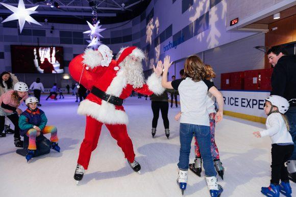 Santa with his Christmas presents sack iceskating on an ice rink and saying hello to kids