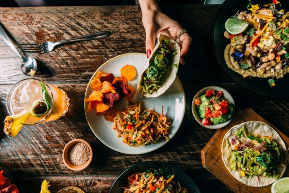 A hand holding a taco over a series of different Mexican dishes on a wooden table