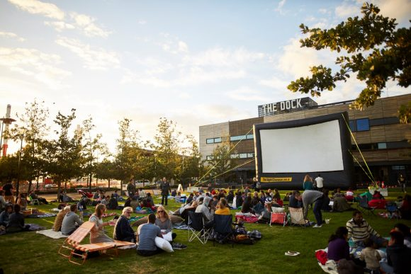A crowd of people sitting in front of a big cinema screen in a park