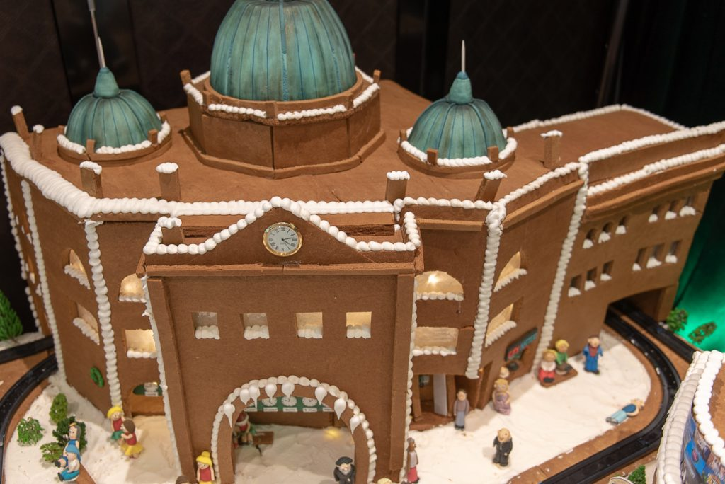 A model of an old fashioned train station made out of gingerbread with tiny marzipan people in front of it