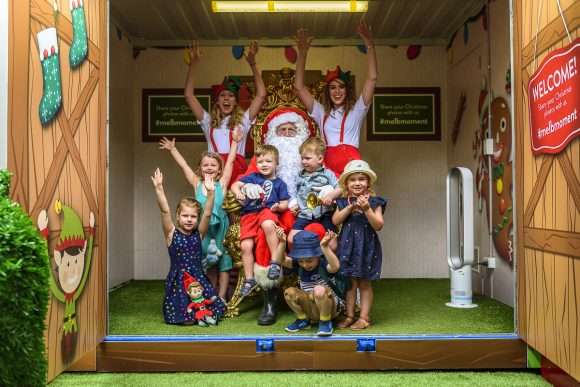 A group of kids sitting with santa and his helpers