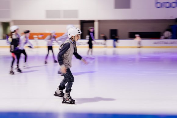 A person ice skating on an indoor ice rink