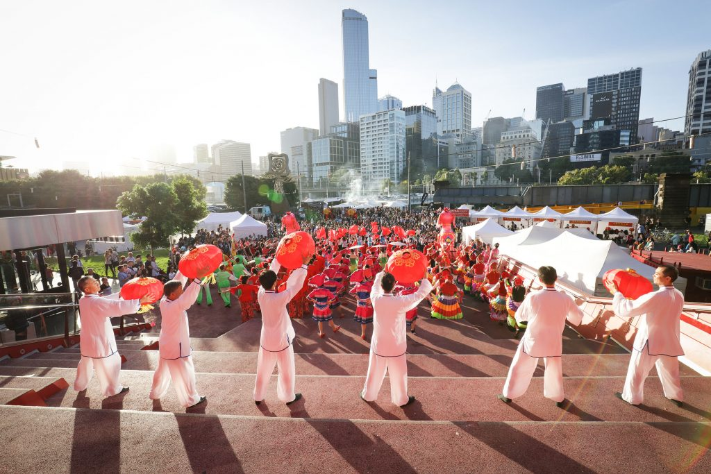 Six men dressed in white, waving red lanterns before a sea of people in front of the city skyline