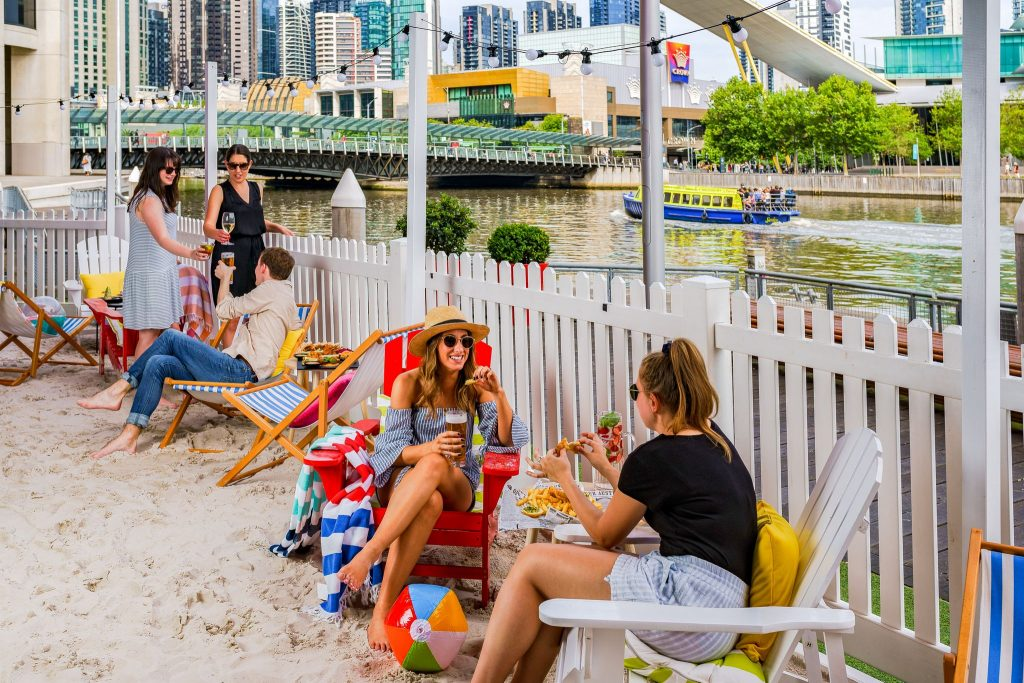 People sitting on deck chairs in the sand in front of a white picket fence, with water behind them