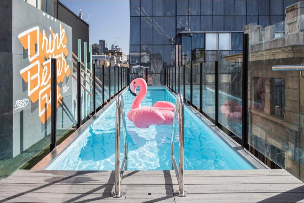 Adelphi Rooftop pool with a large inflatable pink flamingo floating in the middle