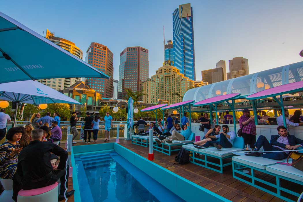 People standing around and lounging on day beds next to a paddling pool with umbrellas. The city skyline is in the background while the sun sets