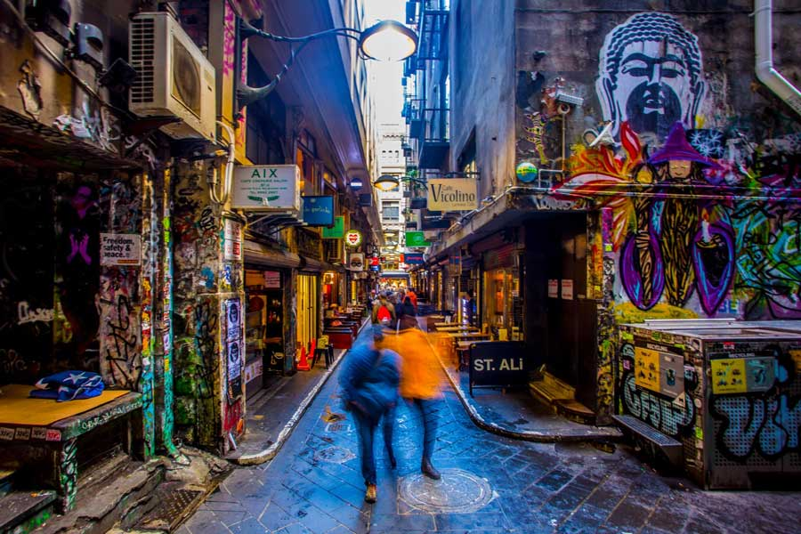 People walking through a street art covered laneway