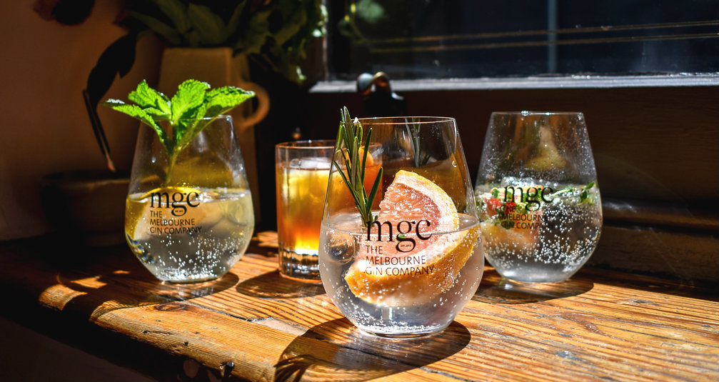 Four gin cocktails on a bench