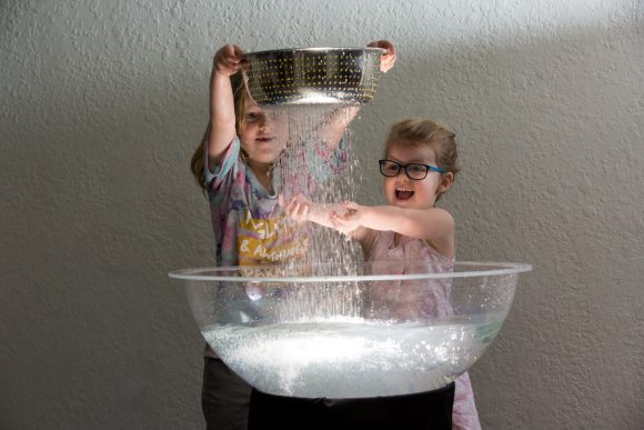 Tow kids standing in front of a bowl of water. One child is holding a strainer with water pouring through onto the hands of the other child.