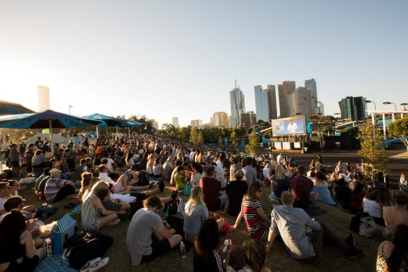 A crowd of people sitting on a lawn watching a big screen with the city skyline in the background