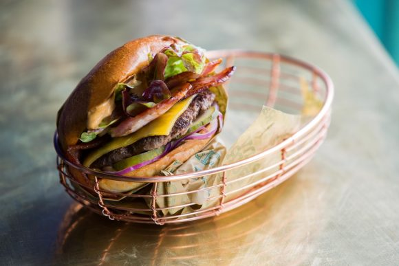 A large multi layer burger in a copper basket